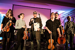 """© Licensed to London News Pictures . 14/08/2015 . Manchester , UK . Poet MIKE GARRY (centre) performs single """" St Anthony : an ode to Anthony H Wilson """", written by Garry and composer Joe Duddell , with the Cassia String Quartet . A tribute to Tony Wilson at Old Granada Studios . Photo credit : Joel Goodman/LNP"""