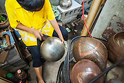 "03 DECEMBER 2012 - BANGKOK, THAILAND:  A woman makes monks' bowls, called ""bat"" (pronounced with a long ""a"" as in baat) on Soi Baan Bat in Bangkok. The bowls are made from eight separate pieces of metal said to represent the Buddha's Eightfold Path. The Monk's Bowl Village on Soi Ban Baat in Bangkok is the only surviving one of what were originally three artisan's communities established by Thai King Rama I for the purpose of handcrafting ""baat"" the ceremonial bowls used by monks as they collect their morning alms. Most monks now use cheaper factory made bowls and the old tradition is dying out. Only six or seven families on Soi Ban Baat still make the bowls by hand. Most of the bowls are now sold to tourists who find their way to hidden alleys in old Bangkok. The small family workshops are only a part of the ""Monk's Bowl Village."" It is also a thriving residential community of narrow alleyways and sidewalks.  PHOTO BY JACK KURTZ"