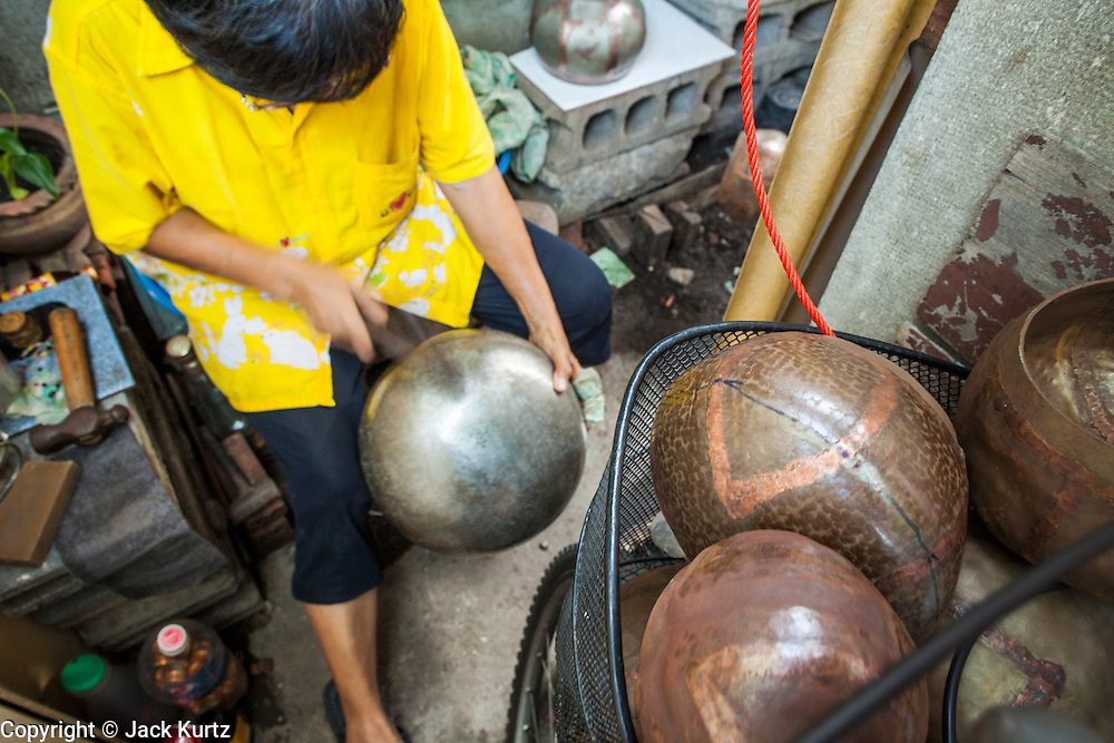 """03 DECEMBER 2012 - BANGKOK, THAILAND:  A woman makes monks' bowls, called """"bat"""" (pronounced with a long """"a"""" as in baat) on Soi Baan Bat in Bangkok. The bowls are made from eight separate pieces of metal said to represent the Buddha's Eightfold Path. The Monk's Bowl Village on Soi Ban Baat in Bangkok is the only surviving one of what were originally three artisan's communities established by Thai King Rama I for the purpose of handcrafting """"baat"""" the ceremonial bowls used by monks as they collect their morning alms. Most monks now use cheaper factory made bowls and the old tradition is dying out. Only six or seven families on Soi Ban Baat still make the bowls by hand. Most of the bowls are now sold to tourists who find their way to hidden alleys in old Bangkok. The small family workshops are only a part of the """"Monk's Bowl Village."""" It is also a thriving residential community of narrow alleyways and sidewalks.  PHOTO BY JACK KURTZ"""