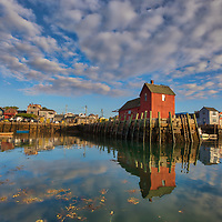 New England sunrise photography of the famous red fishing shack Motif #1 in Rockport, Massachusetts on Cape Ann. The photograph captures the local fishing boats with the iconic landmark and a stunningly beautiful sunrise sky. The historic landmark is known throughout New England as Motif #1, so called because it is the most often painted building in America.<br />