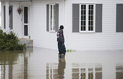 A woman stands in floodwaters surrounding a house in the town of Hudson, Quebec, Canada., west of Montreal, Monday, May 8, 2017, following flooding in the region. Photo by Graham Hughes /The Canadian Press/ABACAPRESS.COM