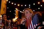 A US citizen listens spellbound to Barack Obama's inauguration speech. Along with other members of expatriate 'Democrats Abroad' party supporters, she holds the American flag during Obama's swearing in as the United States' 44th President, after his Nov 08 election victory as America's first African American Commander in Chief. The location is The Texas Embassy Texmex bar in central London, England. Similar events were held by Democrats Abroad around the world but in England, Obama's election to the White House excited Britain's political and cultural landscape during a deep economic recession.