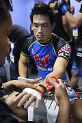 """Hiroshe Tanaka, All-Japan combat wrestling Champion, gets his hands bandaged up<br /><br />MMA. Mixed Martial Arts """"Tigers of Asia"""" cage fighting competition. Top professional male and female fighters from across Asia, Russia, Australia, Malaysia, Japan and the Philippines come together to fight. This tournament takes place in front of a ten thousand strong crowd of supporters in Pelaing Stadium. Kuala Lumpur, Malaysia. October 2015"""
