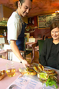 Gruissan village. La Clape. Languedoc. A waiter coming with the fish served for main course. Restaurant La Cranquette. Grilled fried Saucanelles baby-dorade seabream on a skewer. France. Europe.