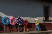 A cowboy stands with flowers next to colorful memorial wreaths on sale for the Day of the Dead festival along a street in Santa Clara del Cobre, Michoacan, Mexico.
