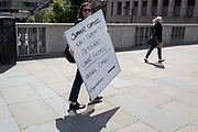 A lady walking over London Bridge carries a business white board with details for summer coffees, on 17th June 2019, in London, England.