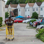 WASHINGTON, DC - JUNE 15: Robert Wells, 12, rides a shopping cart in Congress Heights in Washington, DC, on June 15, 2020. (Photo by Craig Hudson for The Washington Post)