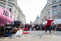 London, UK. 15th April 2019. Climate campaigners enjoy a display by Josh from Bristol around the Ship of Truth at Oxford Circus on the first day of 'International Rebellion UK - Shut Down London!' events to call on the Government to take urgent action to address climate change.