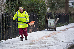 © Licensed to London News Pictures. 09/02/2021. London, UK. A council worker spreads grit on the pavement at Primrose Hill in Camden, North London as snow continues to fall in the capital. Strong easterly winds from Ukraine and the Black Sea are expected to last in to the middle of the week. Photo credit: Ben Cawthra/LNP