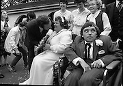 Historic Wedding Bells For Disabled Couple,  (N81)..1981..20.06.1981..06.20.1981..20th June 1981..Happy wedding bells chimed today for the first disabled couple in residential care to marry in the Republic of Ireland. The happy couple are Marie Skully and Pat Linehan and they were married in a special ceremony in The Cara Cheshire Home in the Phoenix Park. Both Marie and Pat are confined to wheelchairs because of their disabilities. After honeymoon, they will make their home in specially adapted quarters within the Cheshire residence..The Minister for Health, Dr Michael Woods, steals a kiss from the new Mrs Linehan.