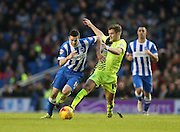 Brighton winger, Jamie Murphy (15) is fouled by Huddersfield Town defender Martin Cranie (14) during the Sky Bet Championship match between Brighton and Hove Albion and Huddersfield Town at the American Express Community Stadium, Brighton and Hove, England on 23 January 2016.