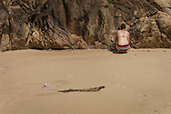 A woman crouches by a rocky facade on a sandy beach of Quy Nhon, Binh Dinh Province, Vietnam, Southeast Asia