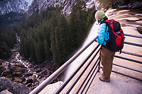Young woman looking over Vernal Falls while hiking the Mist Trail in Yosemite National Park, CA.