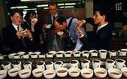 A team of English tea-tasters employed by the tea company Lyons sample different blends for the PG Tips brand in the City of London, England UK. With variously-sourced teas from tea estate plantations, they smell, touch, sip, slurp then spit the hot drink out into a spitoon rather than swallow it many times repeatedly. Britons drink 35 million cups of PG Tips a day and world tea production is approximately 3.2 million tonnes a year. Kenya is the largest producer with Sri Lanka a close second. PG Tips is imported as single estate teas from around the world and blended in precise proportions set by the tea tasters to make blend 777, which can contain between 12 and 35 single estate teas at any one time depending on season..