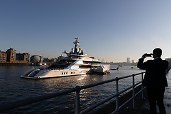 © Licensed to London News Pictures. 04/12/2019. London, UK. A man photographs Dallas Cowboys owner and billionnaire, Jerry Jones's luxury 358 feet (109 meters) superyacht, Bravo Eugenia, which is seen moored at Butlers Wharf, near Tower Bridge on the River Thames after arriving in the capital late yesterday afternoon. The $225 million yacht which was built in 2018 is reported to be named after Jerry Jones's wife, Eugenia and have multiple luxuries onboard including two helipads, a fitness centre and sauna, and is capable of sleeping up to 14 people who are taken care of by a 30-person crew. Photo credit: Vickie Flores/LNP