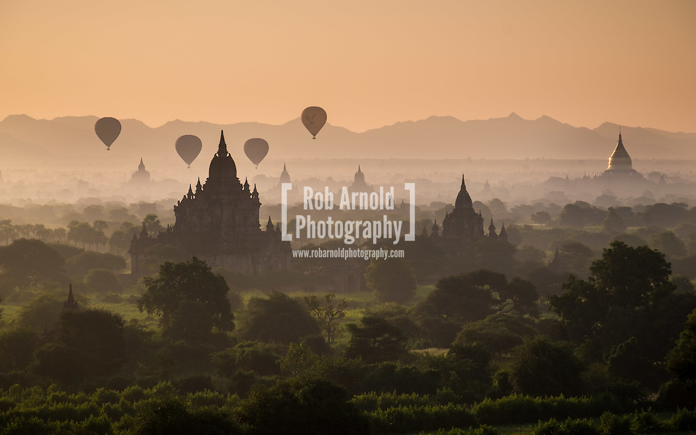 Sunrise over the ancient temples scattered through the Bagan landscape as hot air balloons fly overhead.