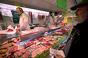 Jörg Melander buys meat from a butcher's trailer at the outdoor market in Ahrensburg, Germany. (Supporting image from the project Hungry Planet: What the World Eats.)