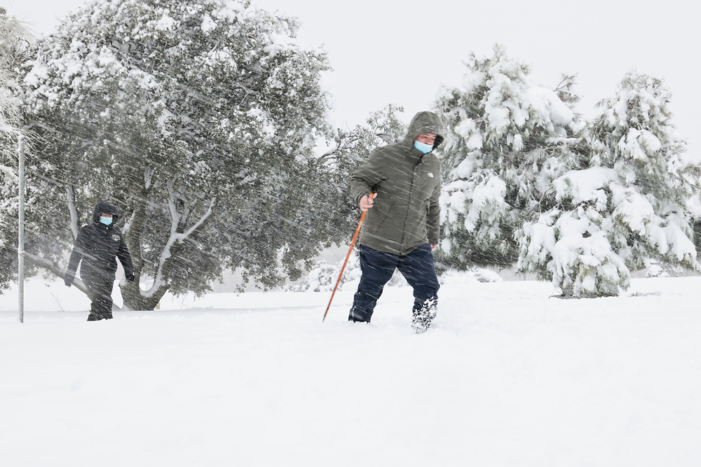 MADRID, SPAIN - JANUARY 9: A couple struggles to walk on the streets covered in snow in a residential area as storm Filomena hits the area on January 9, 2021, in Majadahonda, Madrid, Spain.