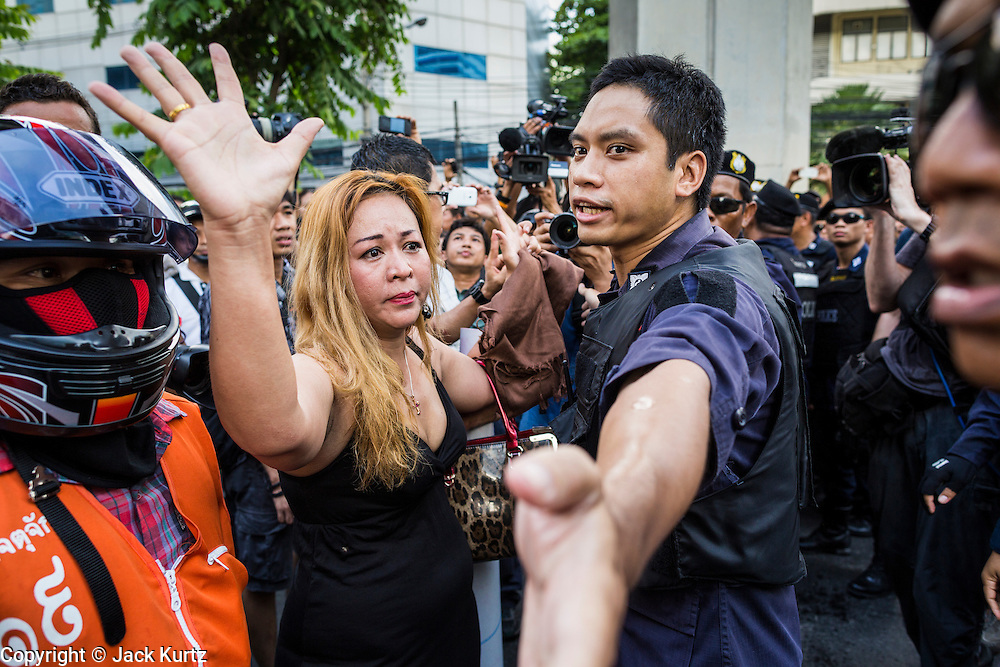 24 MAY 2014 - BANGKOK, THAILAND:  An anti-coup protestor confronts police at a police roadblock in Bangkok. There were several marches in different parts of Bangkok to protest the coup that unseated the popularly elected government. Soldiers and police confronted protestors and made several arrests but most of the protests were peaceful. The military junta also announced that firing of several police commanders and dissolution of the Thai Senate. The junta also changed its name from National Peace and Order Maintaining Council (NPOMC) to the National Council for Peace and Order (NCPO).   PHOTO BY JACK KURTZ