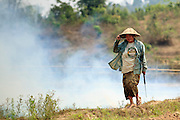 Mar. 12, 2009 -- BAN THO THAN, LAOS:  A peasant woman walks away from her cucumber field after setting it on fire to burn out the dead weeds and plants prior to replanting it. Fire is frequently used to clear the farm fields of Laos before the plating season leaving the skies in March and early April smoky until the monsoon starts in late April.  Photo by Jack Kurtz