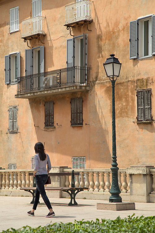 Woman walking by building on town square, Corte, Corsica, France