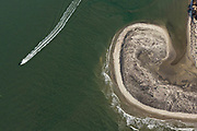 A boat passes a sand swirl on the southwest end of Folly Beach, South Carolina known locally as the Edge of America.