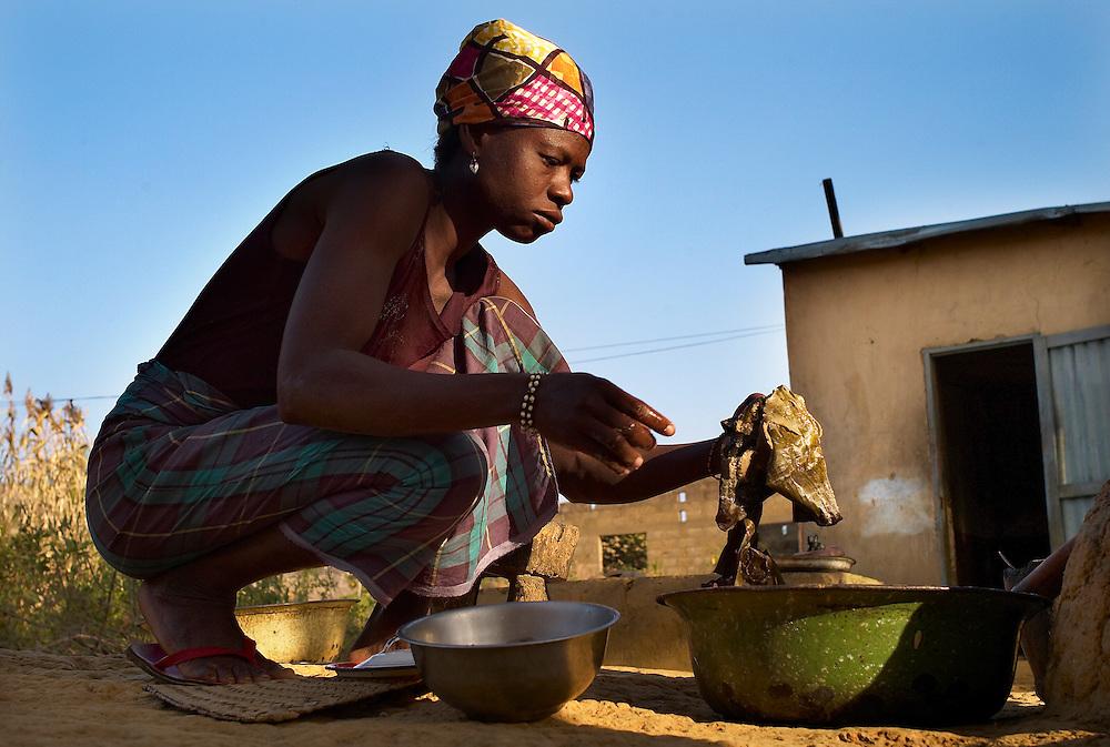 Natitingou November 2006 - Beninese woman preparing food over a fire in front of her house in Natitingou, In Benin .