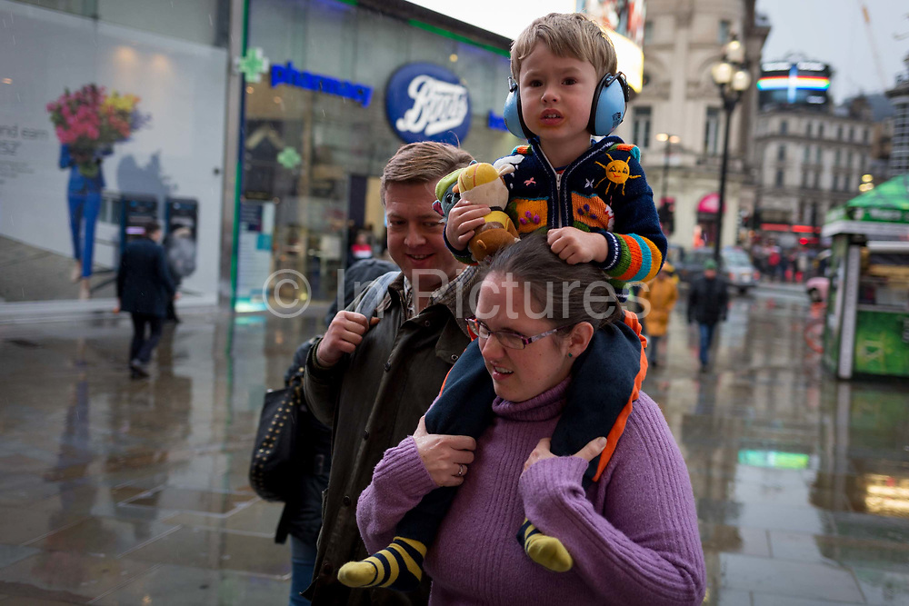 A lady carries a young child on her shoulders during a rain show at Piccadilly Circus in the West End, on 12th November 2019, in London, England.