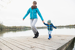 Smiling mother with son walking on wooden jetty over lake