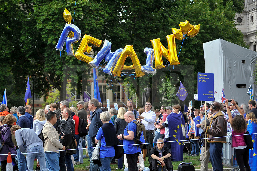 © Licensed to London News Pictures. 09/09/2017. London, UK. An Anti-Brexit protester holds up balloons spelling the word 'REMAIN' in Parliament Square during the People's March for Europe rally campaigning for the UK's continued membership of the European Union. Photo credit : Stephen Chung/LNP