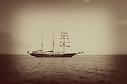 A masted sailing ship cruising through the waters near Floreana Island, the Galapagos Archipelago - Ecuador.