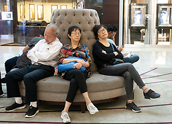 Chinese tourists sleeping inside the Dubai Mall, Dubai, United Arab Emirates, UAE