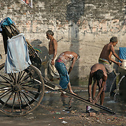 """Rickshaw pullers taking a bath on the streets of Kolkata...The hand-pulled rickshaw of Calcutta, immortalised by Dominic Lapierre's famous novel, City of Joy, will soon be a part of the history books as a bill passed by the West Bengal state assembly described the centuries-old mode of transport as """"inhumane."""".The future of about 18,000 rickshaw pullers in the city, earning an avarage daily wages of about 100 rupees ($2.5).is unclear as they call for a compensation package to help them rehabilitate into alternative jobs."""