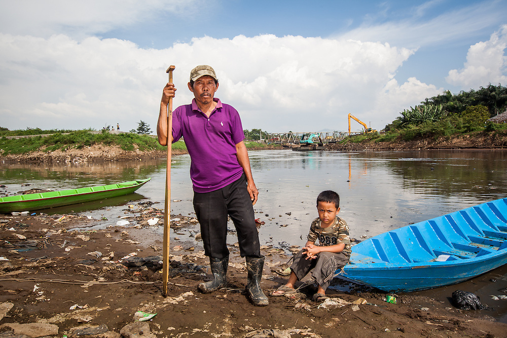 Portrait of Abah Dayat (61) and his Grandson, Fazril (5).  Abah Dayat is a former fisherman but now he collects scrap from the Citarum River since the number of fish had significantly declined due to pollution.  Citeureup Village, Kabupaten Bandung...Credit: Andri Tambunan for Greenpeace