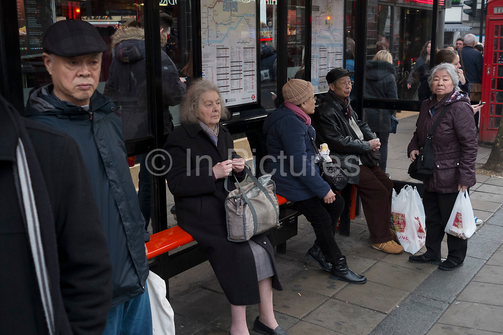Young and old and of many different culturally diverse nationalities, waiting at a bus stop on Charing Cross Road, in the West End of London, England, UK.