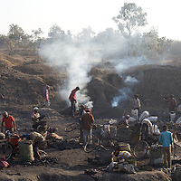 Adivasi miners at work at an illegal coal in Hazaribagh district. The coal is processed into coke at this site and sold for household consumption. Though the mine is illegal the authorities are bribed to turn a blind eye...Photo: Tom Pietrasik.Jharkhand, India.January 29th 2010