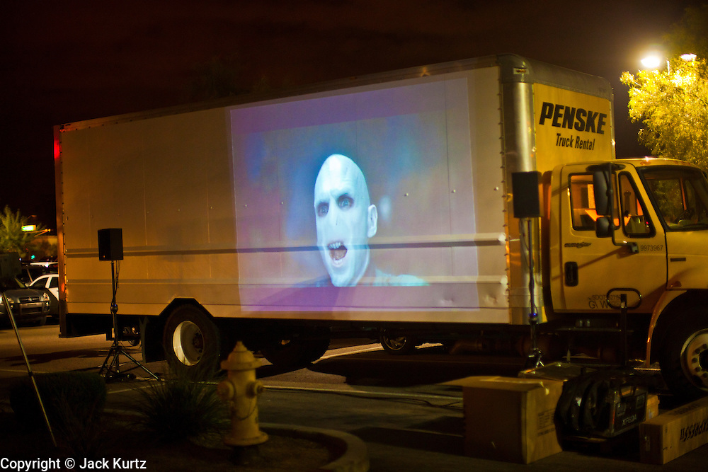 """24 NOVEMBER 2011 - PHOENIX, AZ: A Harry Potter movie is shown on the side of a rented truck at the Best Buy store on Thunderbird and I 17 in Phoenix. """"Black Friday,"""" the unofficial start of the holiday shopping season started even earlier than normal. Many stores, including Target and Best Buy, opened at midnight. The Best Buy at Thunderbird and I 17 showed a Harry Potter movie on the side of a rented truck in the parking lot to keep people amused while they waited for the store to open.   Photo by Jack Kurtz"""