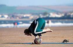 Portobello, Scotland, UK. 18 April 2020. Views of the Portobello promenade and beach on a sunny but cld and windy Saturday afternoon during the coronavirus lockdown in the UK . Woman practices yoga on beach.  Iain Masterton/Alamy Live News
