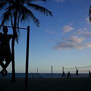 A man works out on a fitness station as a beach volley ball game takes place silhouetted against the late afternoon sky at Ipanema beach. Rio de Janeiro,  Brazil. 4th July 2010. Photo Tim Clayton....