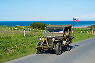 A World War II erea U.S. military jeep drives on a country road in Colleville-sur-Mer, Normandy, France. Omaha Beach, scene of the D-Day landing, is in the background. The driver's hand shows the V-sign