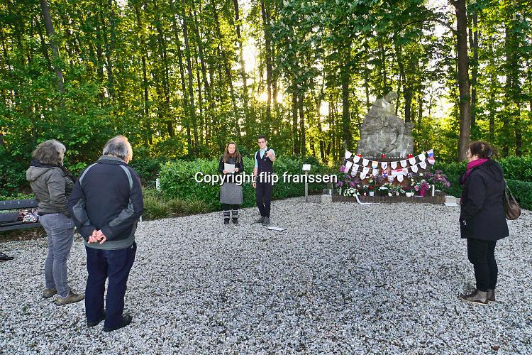 Nederland, Heumen, 4-5-2020 Dorpsdichter de gemeente Heumen Marjolijn Pieks draagt in een live stream gedichten voor na de dodenherdenking . Vanwege de coronamaatregelen zijn er geen georganiseerde bijeenkomsten bij de monumenten en ook hier zijn slecht een handjevol mensen. Kinderen van de basisschool hebben het oorlogmonument van Heumen geadopteerd en brengen elk jaar een eerbetoon aan de vrijheid en de slachtoffers. Het is een monument van Jac Maris ter nagedachtenis aan de nederlandse soldaten van het 1-26 Regiment Infanterie die hier sneuvelden op 10 mei 1940.