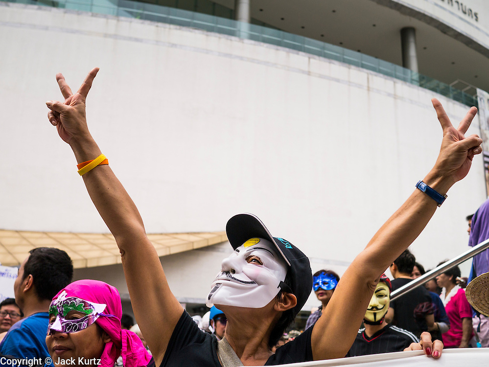 """02 JUNE 2013 - BANGKOK, THAILAND:  An anti-government protester wearing a Guy Fawkes mask during a protest in Bangkok. The so called White Mask protesters are strong supporters of the Thai monarchy. About 300 people wearing the Guy Fawkes mask popularized by the movie """"V for Vendetta"""" and Anonymous, the hackers' group, marched through central Bangkok Sunday demanding the resignation of Prime Minister Yingluck Shinawatra. They claim that Yingluck is acting as a puppet for her brother, former Prime Minister Thaksin Shinawatra, who was deposed by a military coup in 2006 and now lives in exile in Dubai.    PHOTO BY JACK KURTZ"""