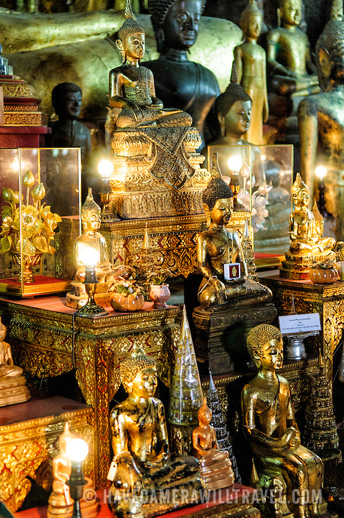 Small statues at the base of the shrine at Wat Mai Suwannaphumaham.  Wat Mai, as it is often known, is a Buddhist temple in Luang Prabang, Laos, located near the Royal Palace Museum. It was built in the 18th century and is one of the most richly decorated Wats in Luang Prabang.