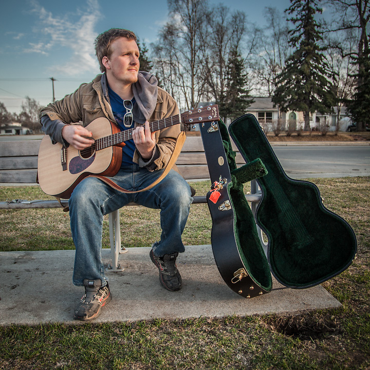 """Musician Ryan Noland with his guitar on the west end of the Delaney Park Strip, Anchorage.  """"For a long time I wanted to be a musician…now I want to start my own construction company…and make some money."""" ranoland8@gmail.com"""
