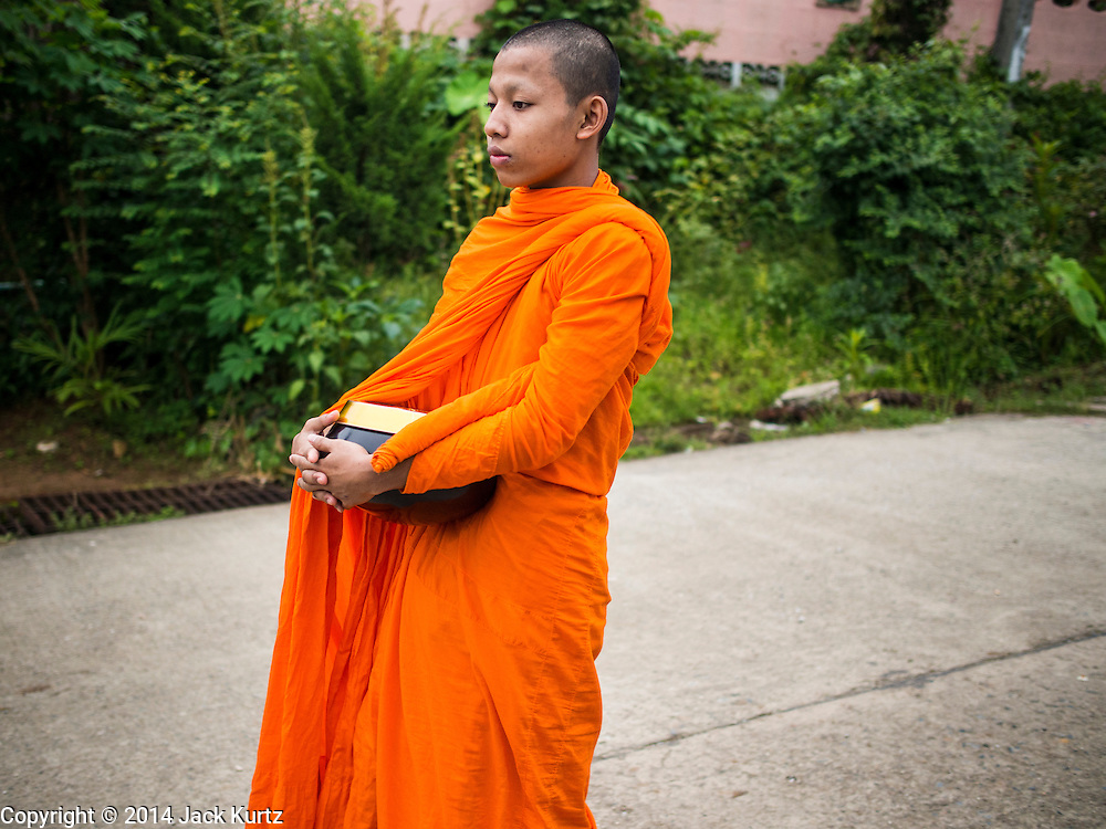 16 SEPTEMBER 2014 - SANGKHLA BURI, KANCHANABURI, THAILAND: A Mon Buddhist monk during the morning alms round in the Mon community in Sangkhla Buri. The Mon were some of the first people to settle in Southeast Asia, and were responsible for the spread of Theravada Buddhism in Thailand and  Indochina. The Mon homeland is in southwestern Thailand and southeastern Myanmar (Burma). The Mon in Thailand traditionally allied themselves with the Thais during the frequent wars between Burmese and Siamese Empires in the 16th - 19th centuries and the Mon in Thailand have been assimilated into Thai culture. The Mon in Myanmar were persecuted by the Burmese government and many fled to Thailand. Sangkhla Buri is the center of Burmese Mon culture in Thailand because thousands of Mon came to this part of Thailand during the persecution.    PHOTO BY JACK KURTZ