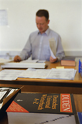 Man working at desk in translation agency office; translating material,