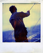 Old Polaroid of a Filipino fisherman standing on a boat, checking the sail support ropes, Palawan Island, Philippines, Southeast Asia