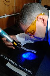 Forensic police officer searches for fingerprints on a plastic bag UK