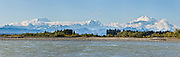 See Mount Foraker, Mount Hunter, and Mount McKinley from the confluence of the Talkeetna and Susitna Rivers at Talkeetna, Alaska, USA. Denali (20,310 feet or 6191 meters, aka Mount McKinley) is the highest mountain peak in North America, and measured from base to peak, it is earth's tallest mountain on land. Mount McKinley is a granitic pluton uplifted by tectonic pressure while erosion has simultaneously stripped away the somewhat softer sedimentary rock above and around it. Panorama stitched from 5 overlapping photos.