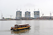 Tour boat on the Singapore River, showing early construction of the three massive towers that now make up the Marina Bay Sands. March, 2009. Singapore